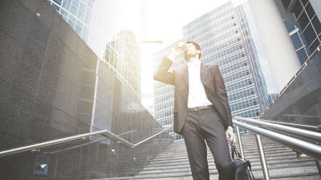 A young businessman dressed in a black suit with white shirt drinks coffee getting down to the metro, on the stairs. Downtown, sunlight, modern buildings on the background
