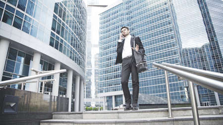 A young businessman dressed in a black suit is talking and solving a question on the phone on the stairs. Downtown and city on the background