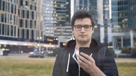Photo pour Man in eyeglasses holding a phone on background of business centre. Man dressed in casual clothes texting in the phone wearing a black hoodie - image libre de droit