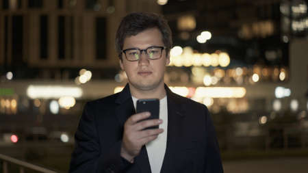 Photo for Businessman in eyeglasses texting on the phone on background of building with yellow lights, bokeh effect. Night shot man in black jacket texting near the road. - Royalty Free Image