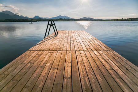 Photo pour Hopfensee with wooden landing stage, in the background the Alp Mountains, Allgäu, Bavaria, Germany - image libre de droit
