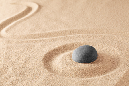 Foto de Mineral stone therapy for a quiet peace of mind through zen meditation and relaxation. Spa wellness or reiki spiritual healing of mind body and soul, mindfulness. Raked sand background with teture and copy space. - Imagen libre de derechos