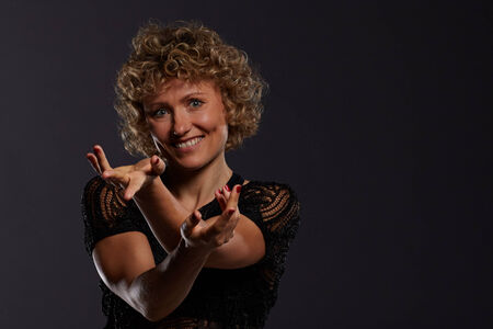 Blonde curly woman twirls her arms