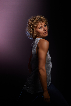 Blonde curly woman facing the shoulder