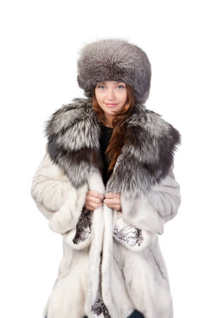 Sexy woman wearing a stylish winter fur coat and hat for protection against the bitter cold on a white background