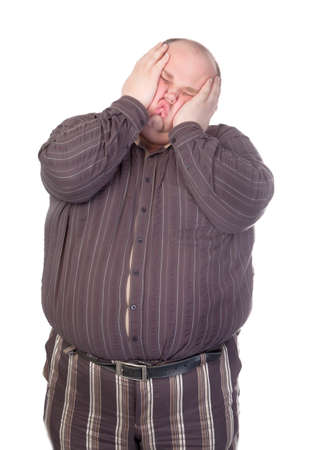 Obese man standing squashing his face with his hands with his buttons popping open over his huge belly isolated on white