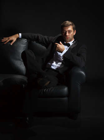 Dramatic portrait of a suave handsome man in a tuxedo and bowtie on couch highlighted in darkness