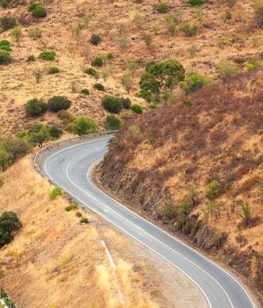 Winding tarred road in the countryside snaking through dry hilly terrain viewed from above