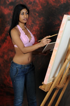 Beautiful young Indian woman working on a canvas