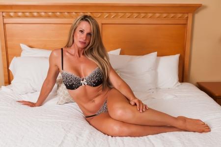 Foto de Beautiful mature blonde in bed in brown lingerie - Imagen libre de derechos