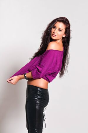 Beautiful tall brunette in a purple tee and black leather pants