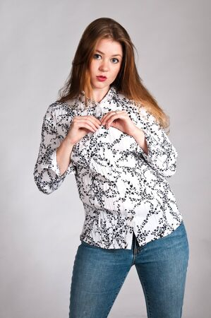 Pretty young brunette in a black and white blouse and jeans