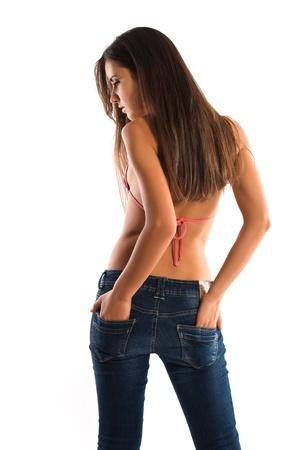 Foto de Beautiful slender Romanian brunette in a bikini top and jeans - Imagen libre de derechos