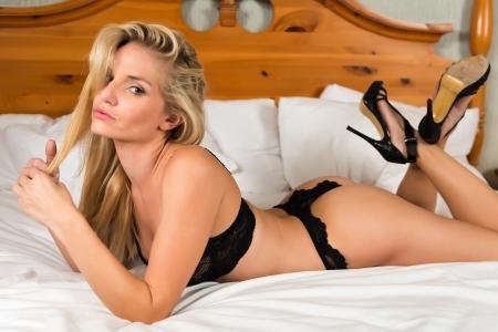 Foto de Pretty young blonde dressed in black lingerie - Imagen libre de derechos
