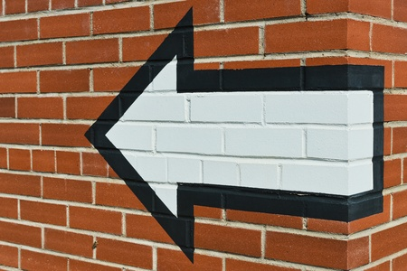 Left direction arrow painted on a brick wall