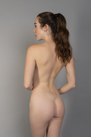 Slender tall young brunette standing nude on gray