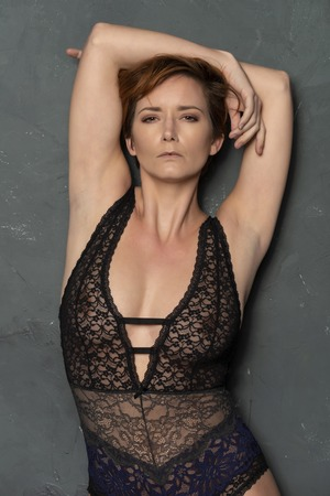 Mature English redhead in a revealing black and blue bodysuit