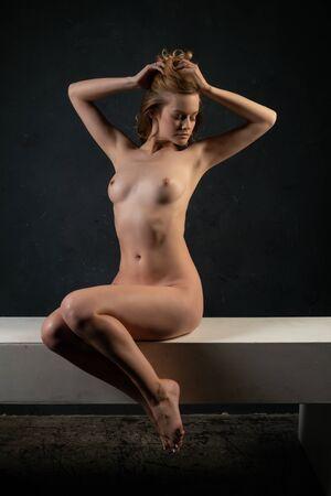 Foto de Beautiful tall blonde woman lying nude on a white beam - Imagen libre de derechos