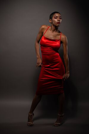 Photo pour Slender young African American woman in a tight red dress - image libre de droit