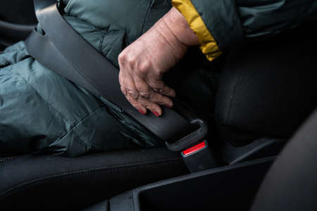 Photo pour Older senior woman fastens a safety belt in a car wearing green and yellow jacket - image libre de droit