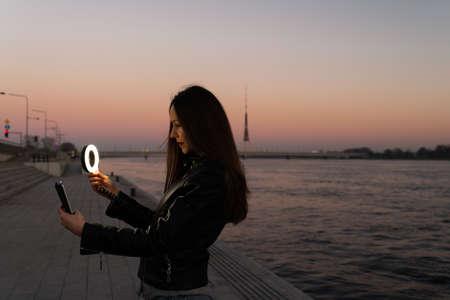 Foto de Young woman taking a selfie using a ring flash as a fill light at a sunset with a view over river Daugava - Imagen libre de derechos