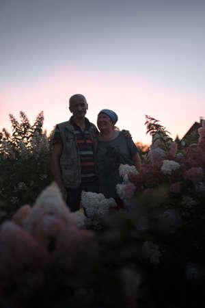 Foto de Elder couple is happy and hugging during violet pink sunset among long hydrangea flowers - Old and loving lovestory - Imagen libre de derechos