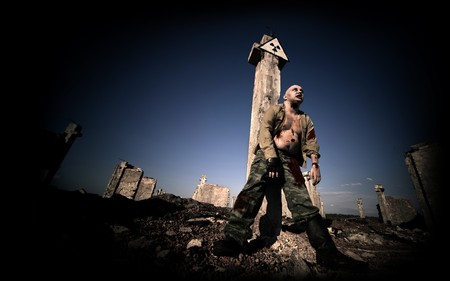 Bloody zombie in the military uniform under the radiation sign on the ruined buildings background.
