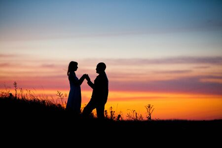 Pretty couple in the meadow on the sunset background.