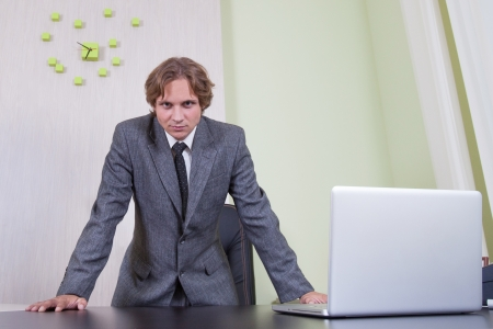Businessman with the laptop on the office background.