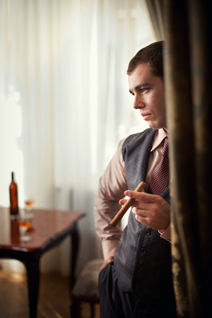 Smart gentleman is going to smoke cigar  Bottle of whiskey with glasses on the background