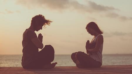 Photo pour Young couple is doing yoga on the sunrise background. Artistic toning. - image libre de droit