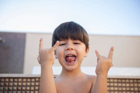 Photo pour Portrait of a boy sticking out his tongue and making the rock and roll symbol with both hands. Boy without a shirt and with a rocker attitude. - image libre de droit