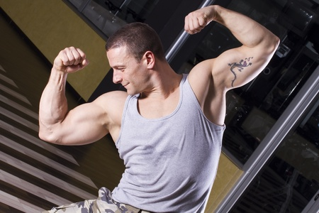 Fitness instructor posing in the gym, showing his muscles