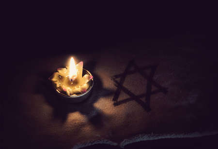 burning candle and the Star of David against a black background.