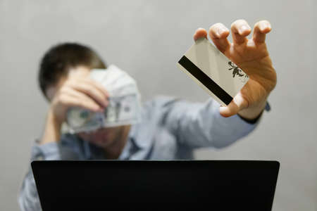 guy holding the credit card in one hand and money in dollars in the other. Sale in online store. The cache-Bek from buying products online.