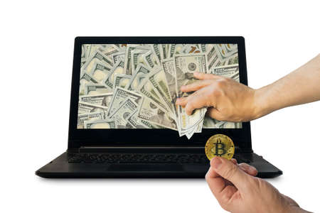 miner earns money by mining the cryptocurrency bitcoin. profit from trading on the stock exchange cryptocurrencies. Gold coin and dollars of bitcoin in the man's hand on the background of the laptop on white isolated background.