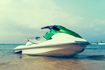 Jet ski moored in shallow water off a beach ready to be taken out to sea by holidaymakers and tourists