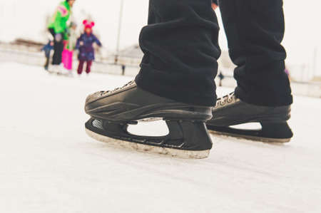 Men\'s feet in ice skating rink in black skates on the background of entertaining people who skate on the rink in the open air.