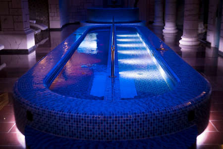 A luxury pillared spa hall with the illuminated plunge pool in the centre. An empty beautiful blue-tiled spa pool of the deluxe hotel. Wall columns sauna design. Illuminated swimming pool in spa