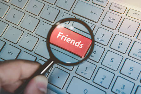 Enlarged through magnifying glass red key Friends on keyboard background. Online searching for friends. A person uses internet to look for buddies. Finding friends in social media. Virtual friends.