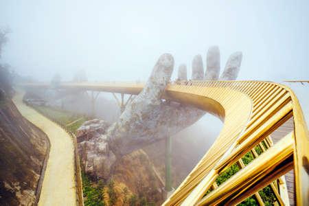 Danang , Vietnam. View in Fog of the Golden Bridge on Ba Na Hills in Da Nang on rainy day.