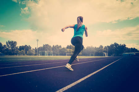 Photo pour young fitness woman runner running on track. A young athlete runs in sportswear at the stadium in the early morning. - image libre de droit