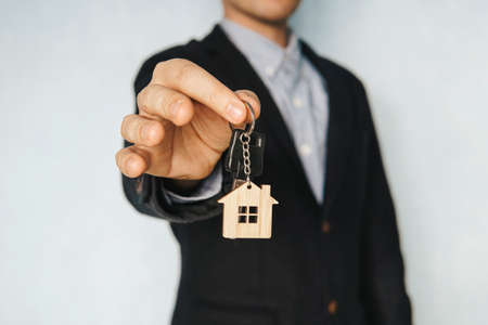 Holding out house keys on a house shaped keychain. concept of selling real estate. Renting an apartment. Rent a room.