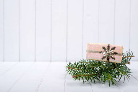 Christmas decoration with fir branches on a white striped background - selective focus, copy space