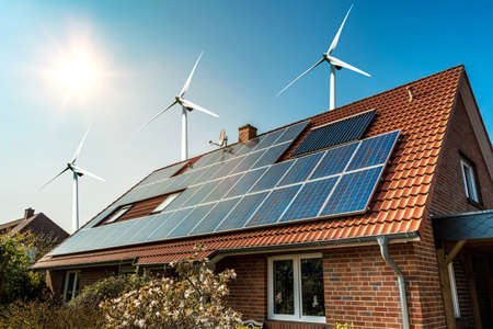 Photo for Solar panel on a roof of a house and wind turbins arround - concept of sustainable resources - Royalty Free Image