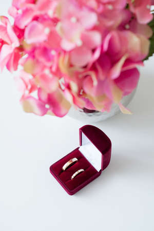 Wedding rings in a red velvet box and bridal bouquet over a white table - selective focus, copy space, vertical, flat lay top-down composition