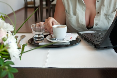 Woman with cup of espresso and laptop