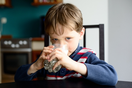 kid boy drinking milk at kitchen table