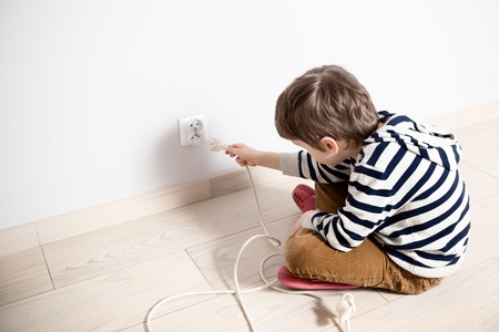 Photo for Curious little boy playing with electric plug. Trying to insert it into the electric socket. Danger at home - Royalty Free Image