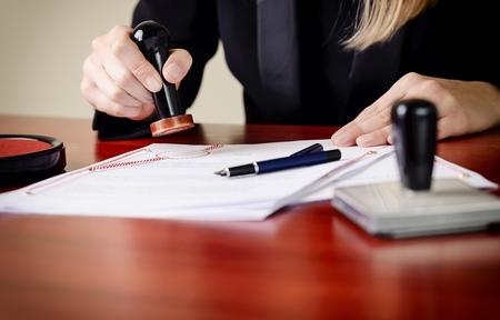 Photo pour Closeup on notary's public hands stamping document. Notary public accessories - image libre de droit